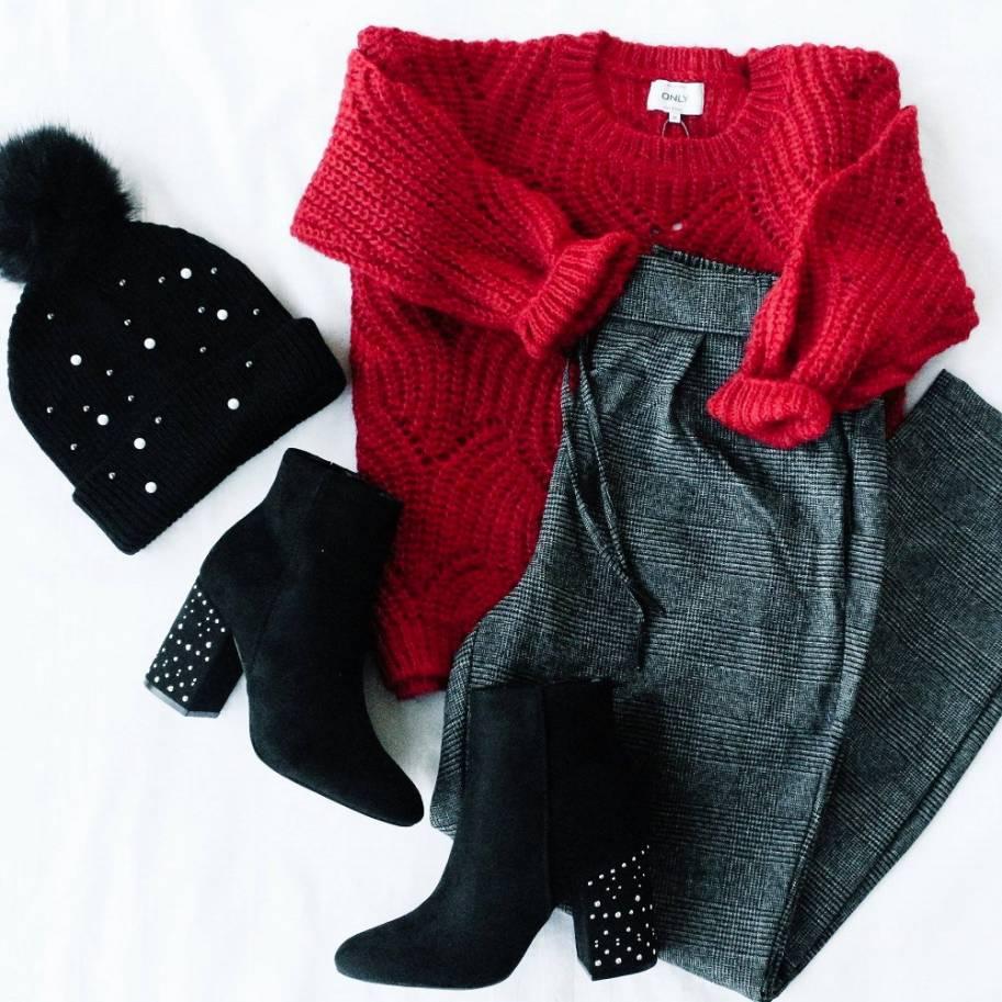 Jersey holgado rojo con pantalon de corte holgado, botas de tacón y gorro con pompón